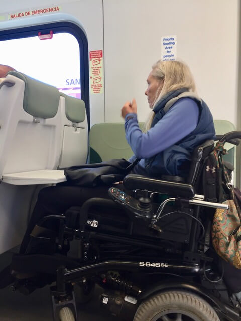A woman in a power chair riding the SMART train