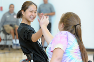 Two girls high five while playing wheelchair basketball at BORP's 2017 Opening Day. Image Courtesy of Scott Goodman