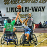 Two kids playing wheelchair basketball; tip off