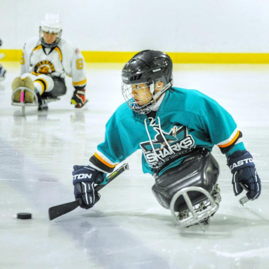 Kid playing sled hockey