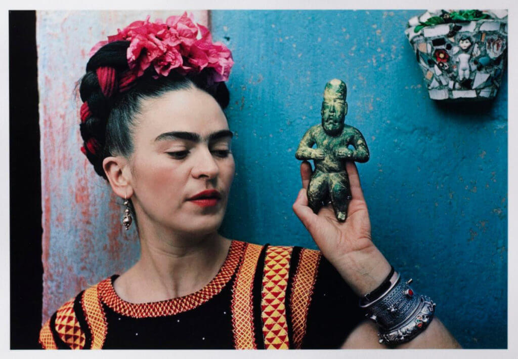 "Frida Kahlo Portrait. Image: Nickolas Muray, ""Frida with Olmeca Figurine, Coyoacán,"" 1939. Color carbon print, 10 3/4 x 15 3/4 in. (27.3 x 40 cm). Fine Arts Museums of San Francisco, Gift of George and Marie Hecksher in honor of the tenth anniversary of the new de Young museum. 2018.68.1. © Nickolas Muray Photo Archives"