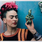 """Frida Kahlo Portrait. Image: Nickolas Muray, """"Frida with Olmeca Figurine, Coyoacán,"""" 1939. Color carbon print, 10 3/4 x 15 3/4 in. (27.3 x 40 cm). Fine Arts Museums of San Francisco, Gift of George and Marie Hecksher in honor of the tenth anniversary of the new de Young museum. 2018.68.1. © Nickolas Muray Photo Archives"""