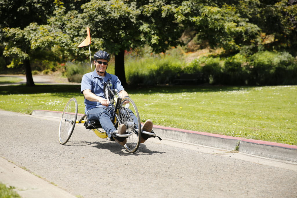 Cyclist rides through the park on his recumbent bike.